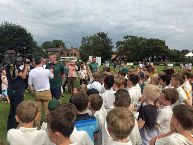 Lindow's James Bracewell being interviewed as the club's juniors look on during World Cup Final day