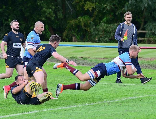 Sam Pemberton dives over for his first of two tries against Burnage, cheered on by Mark Jennings who bagged a hat-trick of scores on his league debut for Wilmslow. Picture: Nick Jones