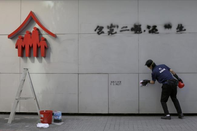 A worker cleans up a vandalised wall in Hong Kong