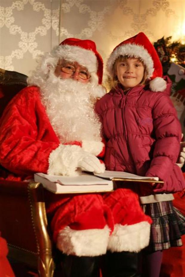 Father Christmas with six-year-old Kirsty Fraser, who won the 'Santa's little helper' competition.