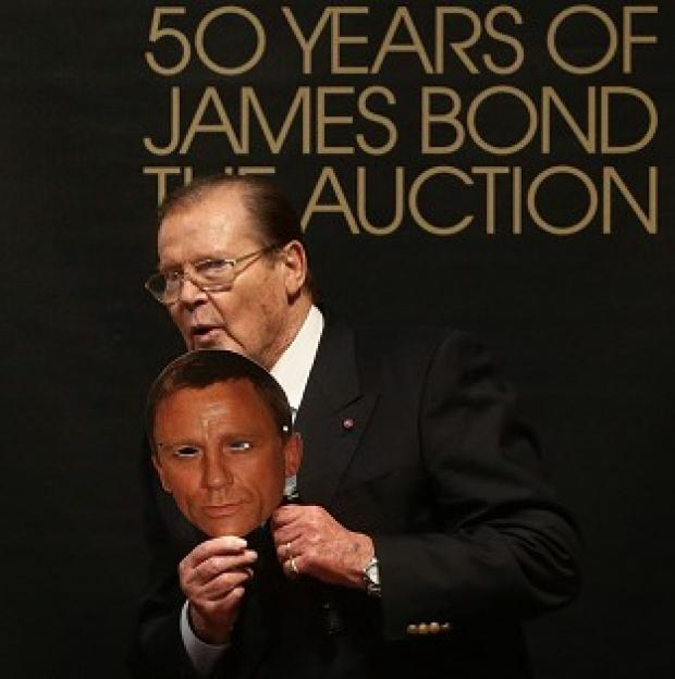 Sir Roger Moore holds a mask of current James Bond actor Daniel Craig at Christie's 50 Years of James Bond Sale