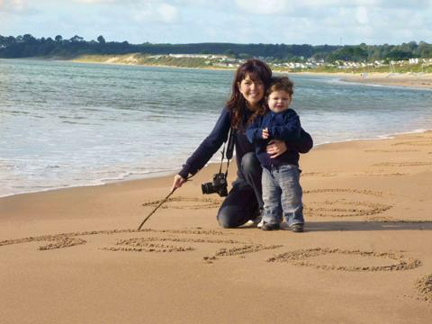 Victoria Pollitt writes names in the sand, helped by her son Joshua, on a beach near Abersoch in north Wales.