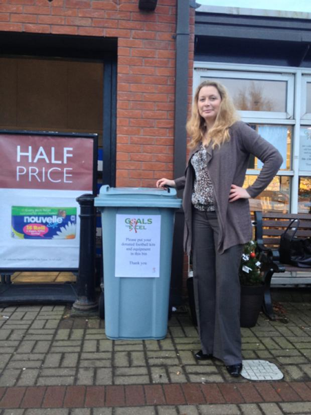 Karen standing next to the football kit bin outside Booths