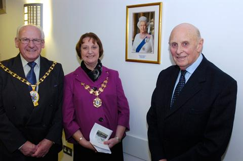 From left, Clr George Walton, mayor of Cheshire East, unveils the portrait of the Queen with help from Knutsford mayor Clr Vivien Davies and Derek Empson, chairman of the Knutsford Old Folks Club Trust
