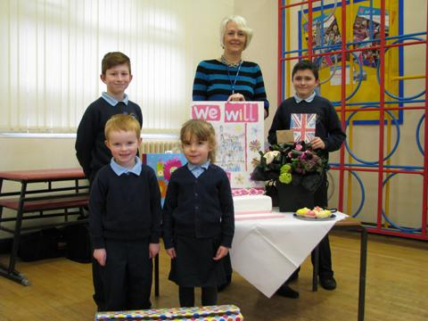 Margaret Jackson with her card from the children and gifts, with school captain Reeve Davies, 10, house captain Jack Gittins, 11, Alex Done, four, and Tawni Davies, four
