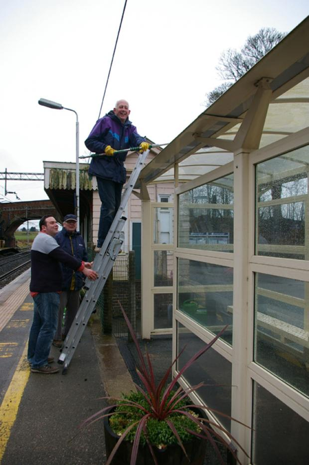 Cleaning the shelter on the Manchester platform. From left, Gavin Hollinshead, Barry Alston and  Peter Godfrey