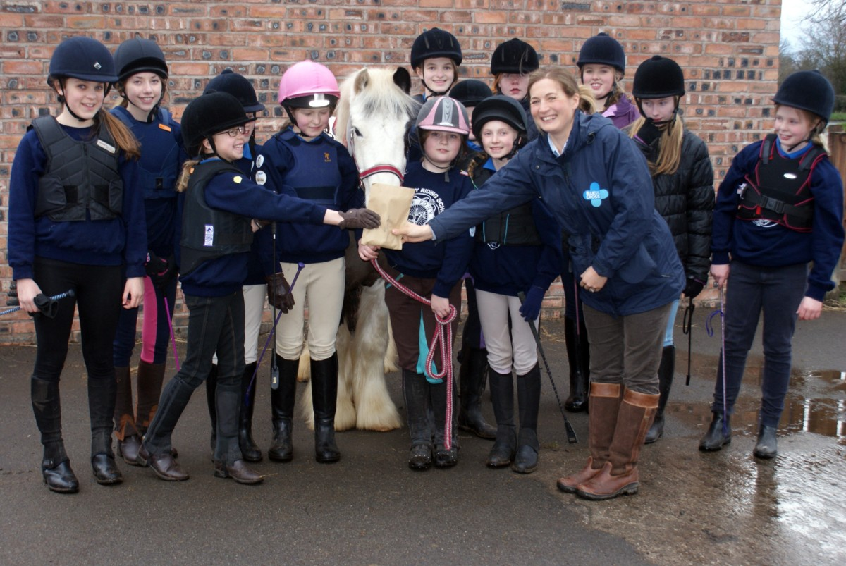 Members of Mobberley Riding School's Pony Club presented the funds to Rebecca Johnson. Also pictured is Sid the resc