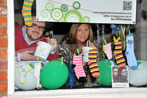 Richard Clare and receptionist Diane Page peep out from the special window display