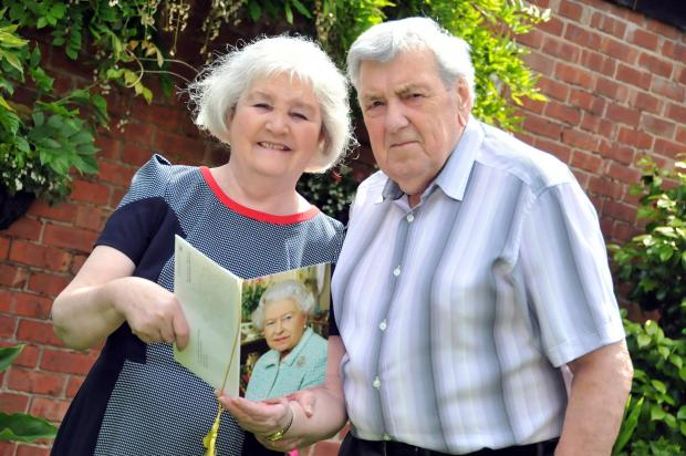 Knutsford Guardian: Mr and Mrs Walsh look at their card from The Queen n142455