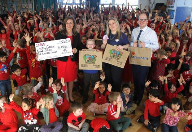 Knutsford Guardian: Charlene Lysaght and Aaron McCaw from the Tesco Extra in Altrincham present Joshua Hill with his winning bag and head teacher Kate Markham with the 500 cheq (002)