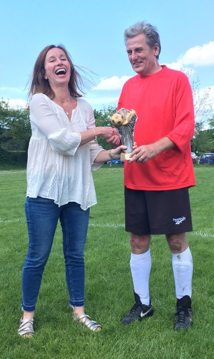Carl Foster, captain of the East team, receives the Simon Weston Trophy from Susie Weston