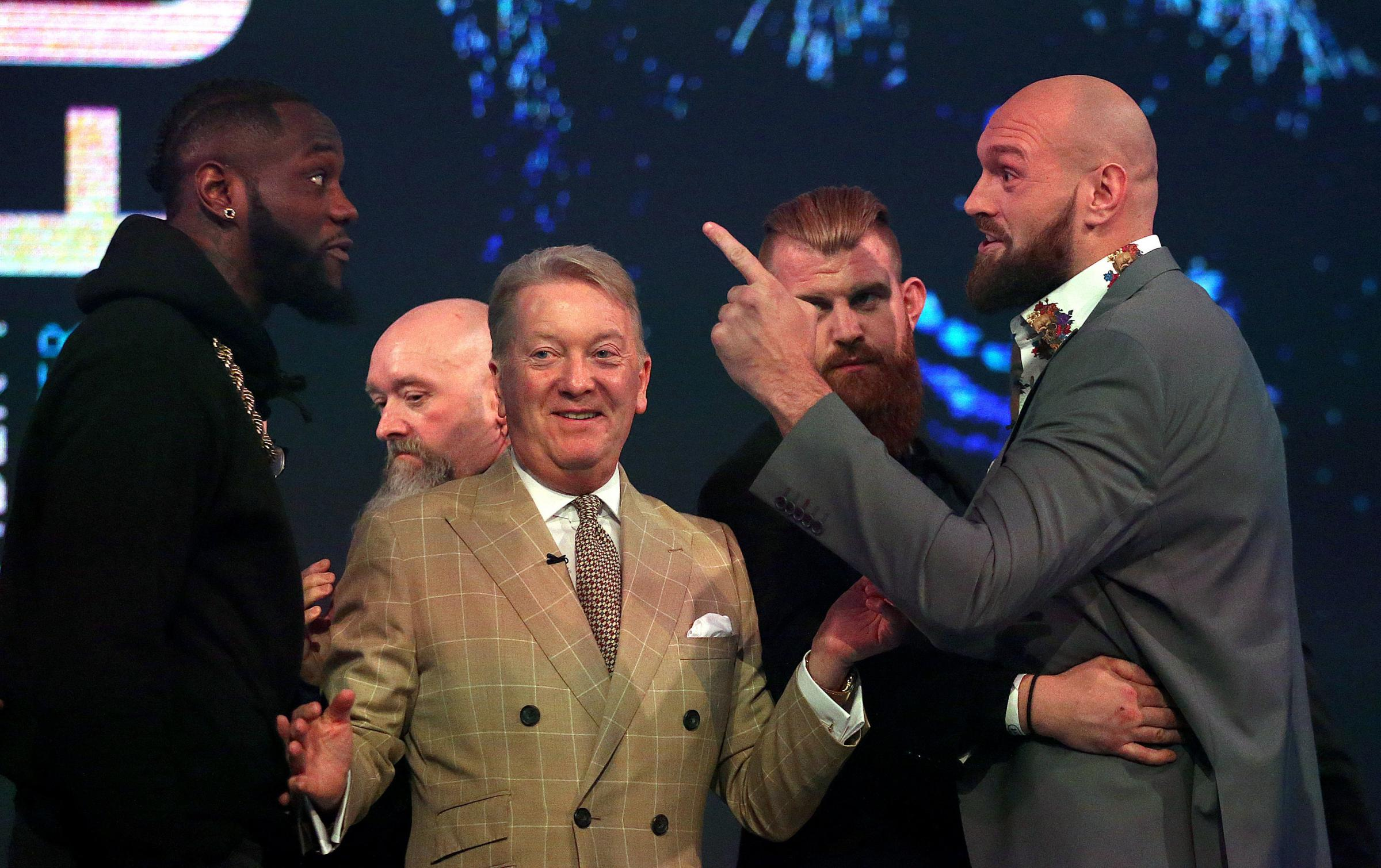 Deontay Wilder, left, and Tyson Fury, right, react as promoter Frank Warren, centre, keeps them apart during a press conference. Picture: Steven Paston/PA Wire