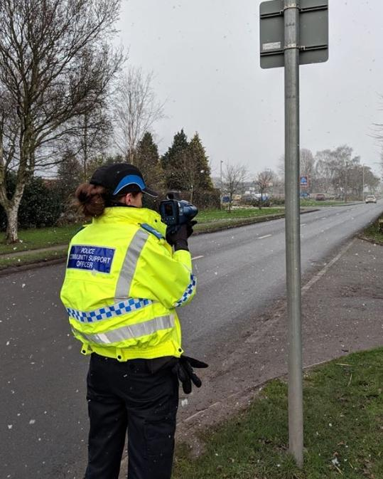 An officer checks traffic speed in Manor Lane