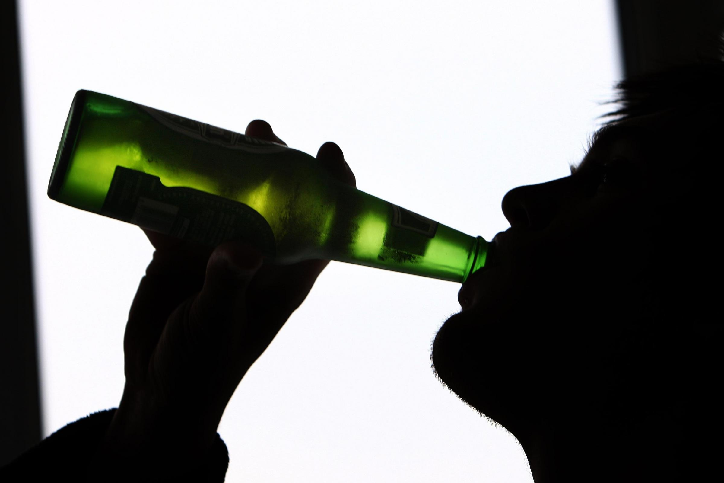A silhouette of a young man drinking alcohol from a bottle