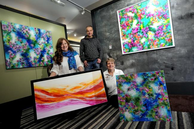 Susi Clarke, left, with the donated painting and other works by her, with Vermilion owner James Blinkhorn and Knutsford First Responder Trust chairman Sal Thompson